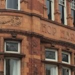Photo of the words Hop Market are embossed in the brick work