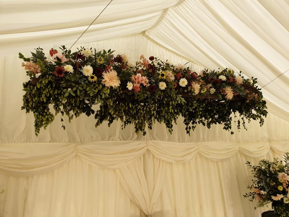 Photo of hop bines and flowers decorating a wedding marquee by Palmers Brewery