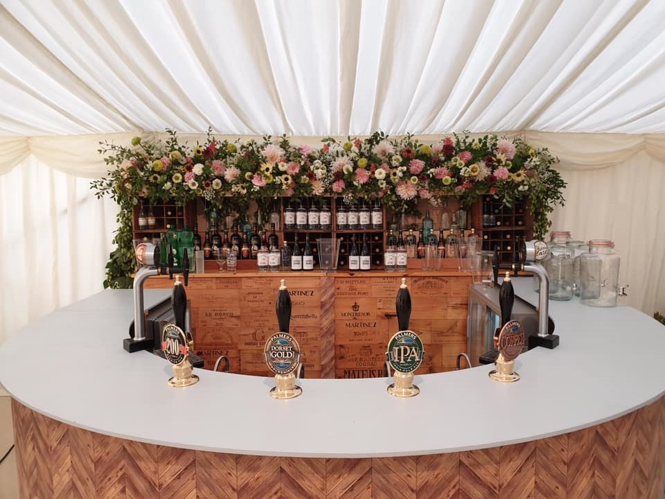Photo of bines and flowers decorating a wedding bar by Palmers Brewery